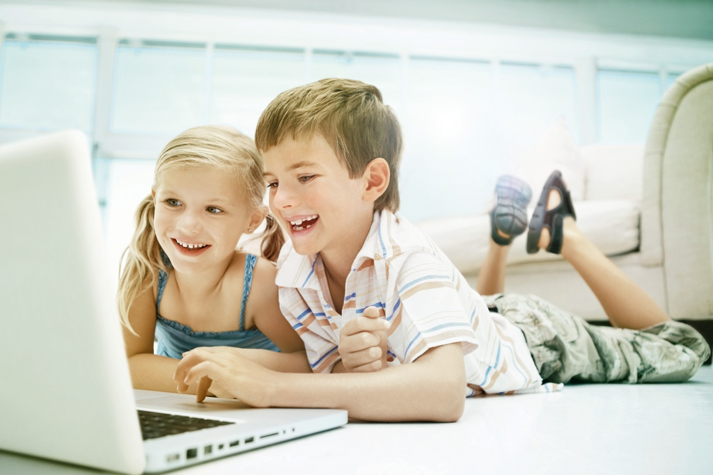 Kids using laptop on floor with parents in the background