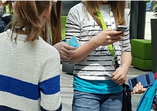 Mädchen mit Smartphone in einer Gruppe