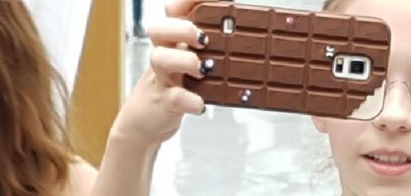 Mädchen mit Smartphone mit Handycover in Form einer Tafel Schokolade