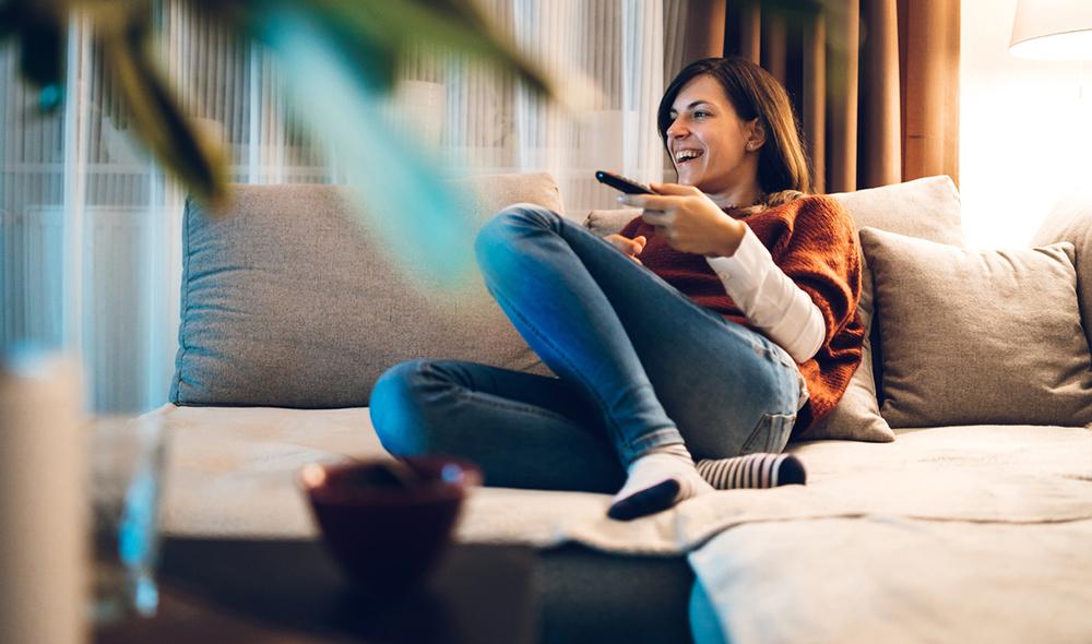 Frau mit Fernbedienung am Sofa