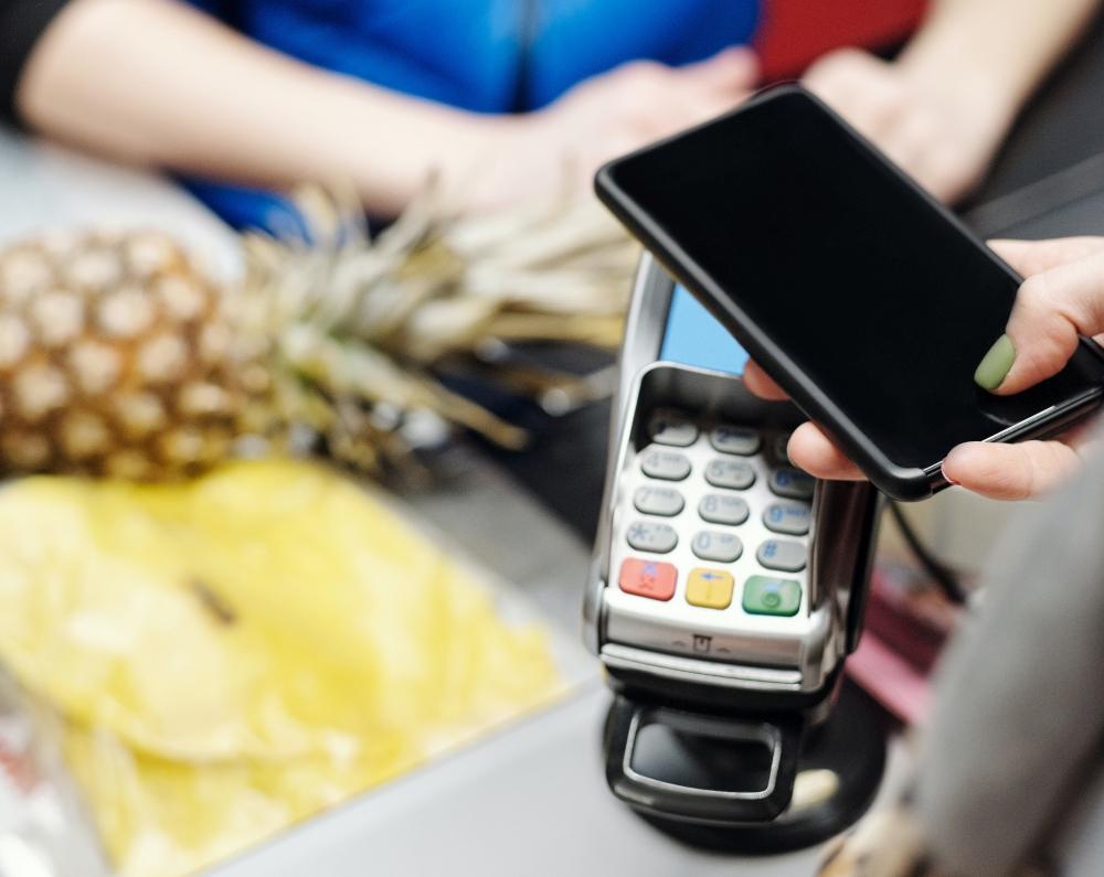 Smartphone vor Bezahlterminal im Supermarkt