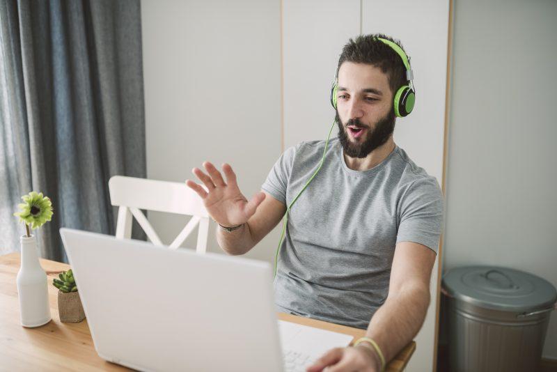 Junger Mann mit Bart telefoniert via Laptop und Kopfhörern