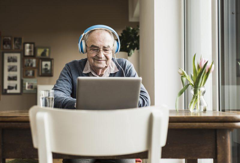 Alter Mann mit Lapdtop und Kopfhörern